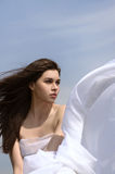 Girl holds fabric in hands waving in the wind. Against the blue sky. She sits on green hill and is wearing in a white loose-fitting clothing. Concept: freedom Stock Photo