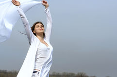Girl holds fabric in hands waving in the wind. Against the blue sky. She is wearing in a white loose-fitting clothing. Concept: ease, health, cleanliness Stock Photos