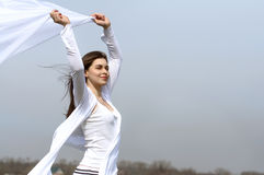 Girl holds fabric in hands waving in the wind. Against the blue sky. She is wearing in a white loose-fitting clothing. Concept: ease, health, cleanliness Stock Image