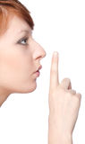 A girl holds a finger to lips gesture silently. Over white background Stock Image