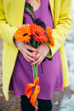 Girl holds flowers, bright colors background. Yellow, orange, purple Royalty Free Stock Photo