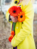 Girl holds flowers, bright colors background. Yellow, orange, purple Stock Photos