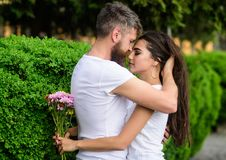 Girl holds flowers while man caress her long hair. Couple in love hugs outdoors park background. Man bearded hipster. Girl holds flowers while men caress her stock photo