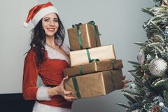 Girl holds four gifts in a gold wrapper in an apartment decorated for the new year. Young woman in red Santa Claus costume pulls royalty free stock photography