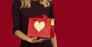 A girl holds a gift with a heart closeup on an isolated red background. Valentine day concept stock photos