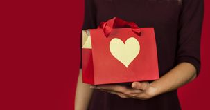 A girl holds a gift with a heart closeup on an isolated red background. Valentine day concept royalty free stock photos