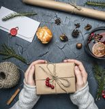 Girl holds a gift for new year or Christmas, an envelope, a mulled wine cup, a packing paper, Christmas trees, mandarins and cin stock photography