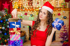 Girl holds gift and points a finger at others Royalty Free Stock Image