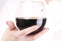 Girl holds a glass in his hand. Girl holds a glass with red wine in his hand Royalty Free Stock Photography