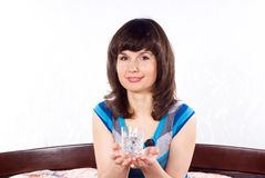 Girl holds a glass of water sitting on the bed Stock Images