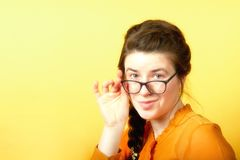 Girl holds glasses with hand on yellow background, concept of office employee about to leave royalty free stock photography