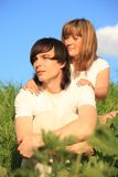 Girl holds guy behind for shoulders Royalty Free Stock Images