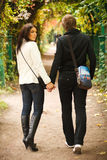 The girl holds the guy by the hand. Two lovers walking  in the autumn garden Royalty Free Stock Photos