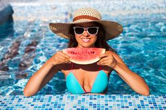 A girl holds half a red watermelon over a blue pool, relaxing o. N spa in a tropical hotel, eating healthy, fruit diet, summer party style royalty free stock photos