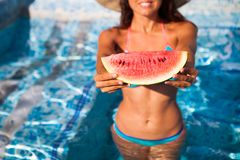 A girl holds half a red watermelon over a blue pool, relaxing o stock image