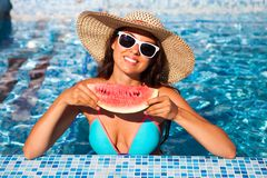 A girl holds half a red watermelon over a blue pool, relaxing o royalty free stock image