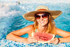 A girl holds half a red watermelon over a blue pool, relaxing o royalty free stock photo