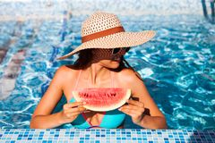 A girl holds half a red watermelon over a blue pool, relaxing o stock photo