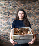 The girl holds in hand a basket with fir cones. The girl holds in hand a basket with fir cones and costs at a brick wall Stock Photo