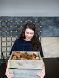 The girl holds in hand a basket with fir cones. Royalty Free Stock Photos
