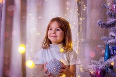The girl holds a Christmas ball in hand. The girl holds in hand a Christmas ball near a Christmas tree Royalty Free Stock Images