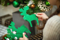 The girl holds in hand a Christmas decor of green deer Stock Image