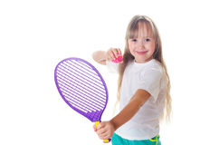 The girl holds in hand a tennis racket with a ball and smiles Royalty Free Stock Images