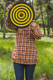 Girl holds in the hands dartboard with arrow in the center target outside in the park Stock Photos