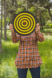 Girl holds in the hands dartboard with arrow in the center target outside in the park Stock Photography