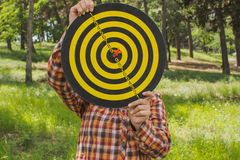 Girl holds in the hands dartboard with arrow in the center target outside in the park Stock Image