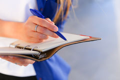Girl holds in hands diary, notebook with sheets and pen and writ Stock Photos