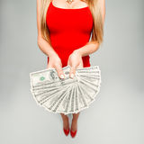 The girl holds in hands a lot of money. The woman in the red dress and red shoes with a fan of banknotes in his hands, his chest. Royalty Free Stock Photography
