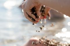 The girl holds in hands pebble stones royalty free stock photography
