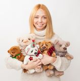 Girl with soft toy bear on white background. The girl holds in hands of toy bears and smiles. Homemade soft toys with their hands Royalty Free Stock Images