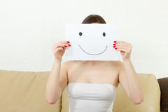 Girl holds happy face drawing. Young smiling woman bears happy face drawing. Female cover her face with joyful teasing smile drawn on paper. Thrilled young royalty free stock photo