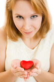 A girl holds a heart in the palms Stock Photography