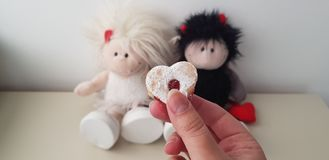 A girl holds heart shaped cookie against twin angel and devil romantic toys stock photography