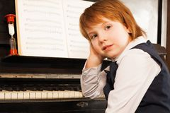 Girl holds her face with hand on the piano Stock Photo