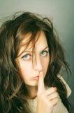 Girl holds her finger on lips Stock Images