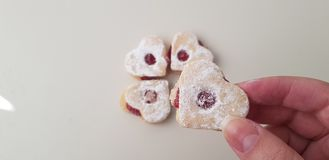 A girl holds in her fingers one heart shaped cookie royalty free stock image