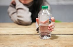 Girl holds in her hand a bottle of water on the table. stock photo