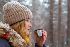 Girl holds in her hand a cup of tea outdoors on a frosty day. Girl holds in her hand a cup of tea thermos cap outdoors on a frosty day royalty free stock images