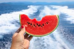 A girl holds in her hand a slice of bitten watermelon on the background of the sea. Taste of summer sea holidays concept royalty free stock image