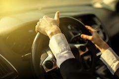 The girl holds her hands behind the wheel of the car royalty free stock image
