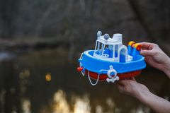 A girl holds in her hands a small toy steamer above a forest stream stock image