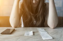 The girl holds her head after counting how much money she spent in the store, on the desk checks and phone, the sun stock images