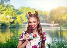 Girl holds a huge chocolate bar. Royalty Free Stock Images
