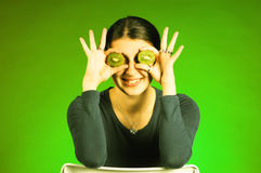 Girl holds kiwi in front of her eyes Royalty Free Stock Photo