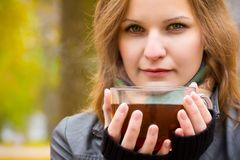 Girl holds large cup with hot tea. Young attractive woman holds mug with hot beverage in autumn park Royalty Free Stock Photo
