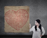 Girl holds love maze puzzle map. Asian girl is holding a love maze puzzle map on brown vintage background Royalty Free Stock Photo